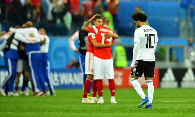 Egypt's Mohamed Salah makes his way off the pitch as two Russia players celebrate at full time. Dylan Martinez / Reuters
