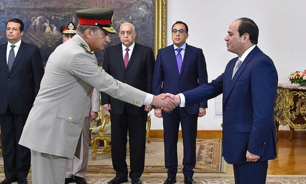 File- Zaki (L) shakes hands with Sisi after being sworn in as defence minister on 14 June (AFP)