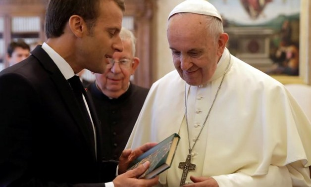 Pope Francis exchanges gifts with French President Emmanuel Macron during a private audience at the Vatican, June 26, 2018. Alessandra Tarantino/ Pool via Reuters