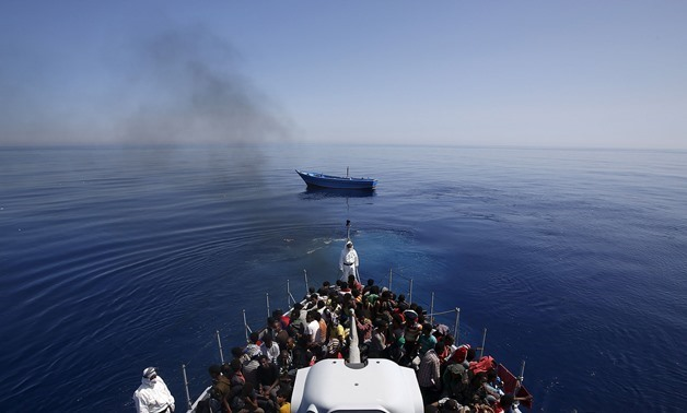 RESCUED: Italian police carry migrants to safety, leaving their leaky boat to drift – REUTERS/Alessandro Bianchi