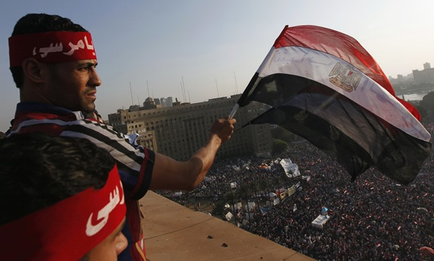 Protesters wave Egyptian flags as demonstrators opposing Egyptian President Mohamed Mursi shout slogans against him and Brotherhood members during a protest at Tahrir Square in Cairo June 30, 2013. REUTERS/Mohamed Abd El Ghany