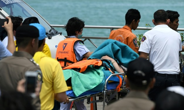 Emergency personnel transfer a passenger from the sunken tourist boat - AFP