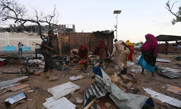 Somali women and security forces search through the damage caused at the scene of a blast near the Mogadishu sea port in Mogadishu, Somalia, May 24, 2017.
