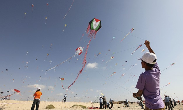 Palestinian children fly kites on the beach of Beit Lahiya in the northern Gaza Strip. Photo by Mohammed Salem/Reuters