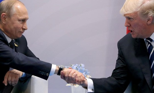 FILE PHOTO: FILE PHOTO: U.S. President Donald Trump shakes hands with Russian President Vladimir Putin during the their bilateral meeting at the G20 summit in Hamburg, Germany, July 7, 2017. REUTERS/Carlos Barria/File Photo/File Photo