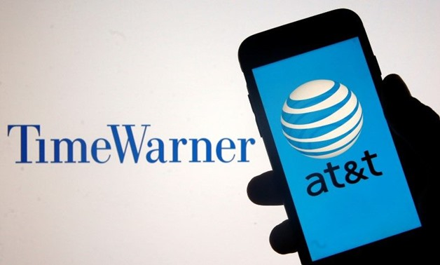 Smartphone with AT&T logo is seen in front of displayed Time Warner logo in this picture - AFP