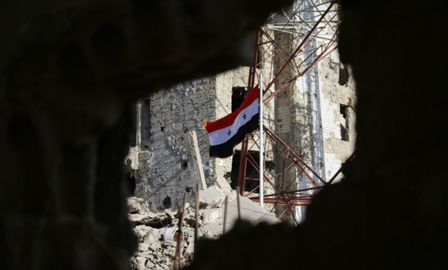 The Syrian national flag flies in the midst of damaged buildings in Daraa-al-Balad, an opposition-held part of the southern city of Daraa, on July 12, 2018