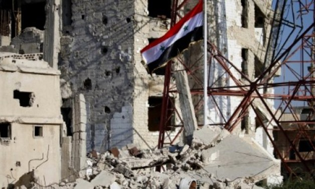 The Syrian national flag flies among damaged buildings in an opposition-held part of the southern city of Daraa on July 12, 2018 - AFP