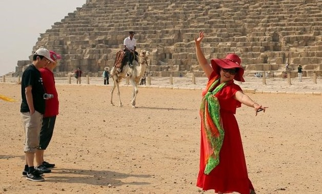 A tourist poses in front of a policeman on a camel at the pyramids plateau