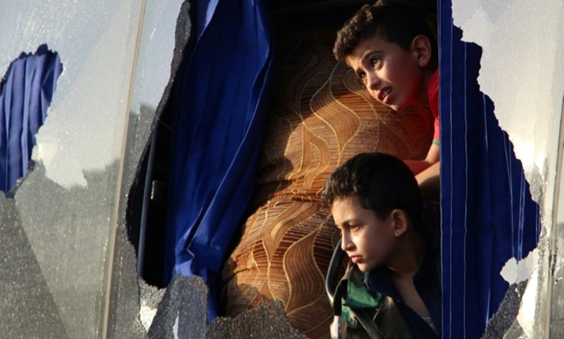 Evacuated Syrians from the area of Fuaa and Kafraya look out of a broken bus window as it passes the Al-Eis crossing south of Aleppo on July 19, 2018