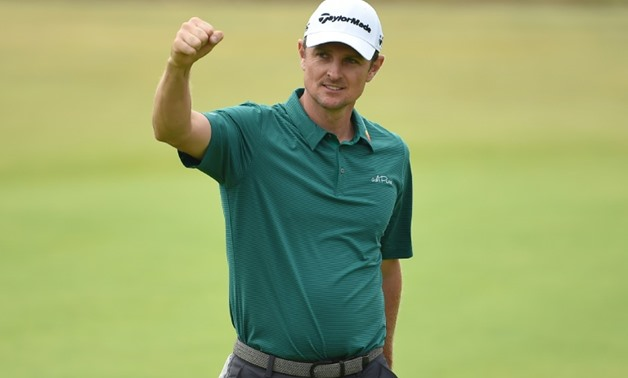 Justin Rose reacts after holing his birdie putt on the 18th green for a third round of 64 on day 3 at Carnoustie AFP / Paul ELLIS