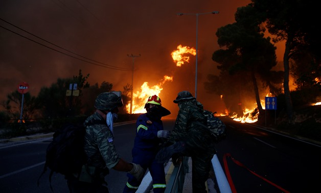 Firefighters and soldiers fall back as a wildfire burns in the town of Rafina, near Athens, Greece, July 23, 2018. REUTERS/Costas Baltas