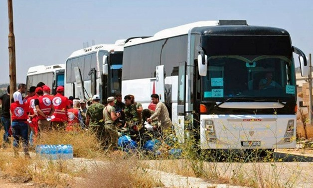 In this photo released by the Syrian official news agency SANA, Syrian government forces and Syrian Arab Red Crescent oversee the evacuation by buses of opposition fighters and their families from the southern province of Daraa, Syria, Sunday, July 15, 20