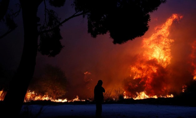 A man looks at the flames as a wildfire burns in the town of Rafina, near Athens, Greece, July 23, 2018. REUTERS/Costas Baltas. ""