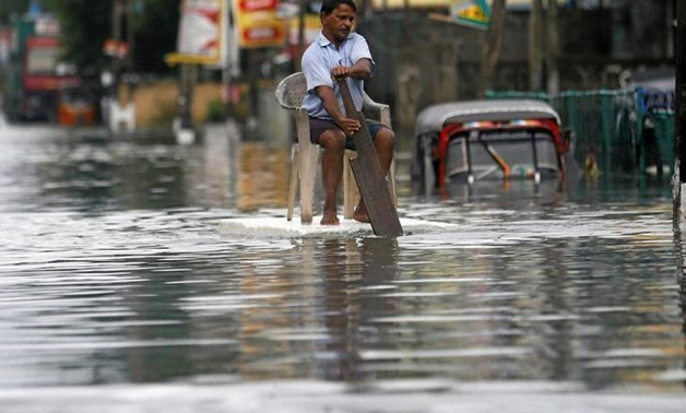 A man sits on a chair as he uses a piece of styrofoam to move through a flooded road in Wellampitiya, Sri Lanka May 21, 2016. REUTERS/Dinuka Liyanawatte
