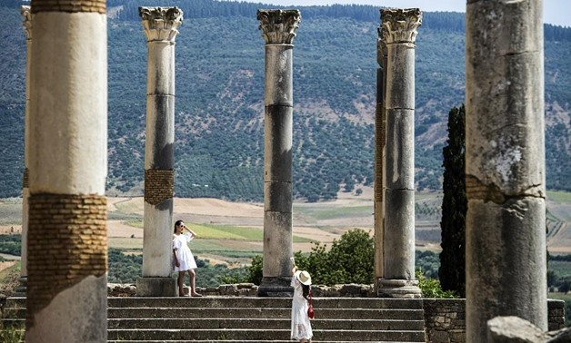 Tourists walk through the ruins of Morocco's oldest Roman site of Volubilis, in the center of a fertile plain at the foot of Mount Zerhounn, on July 25, 2018. Fadel Senna/AFP