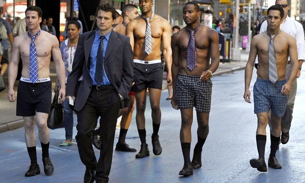 FILES - In this file photo taken on June 27, 2012 male models in underwear follow men in suits around Times Square to promote the Men's Wearhouse national suit drive starting June 27–July 31.  AFP / Timothy A. CLARY