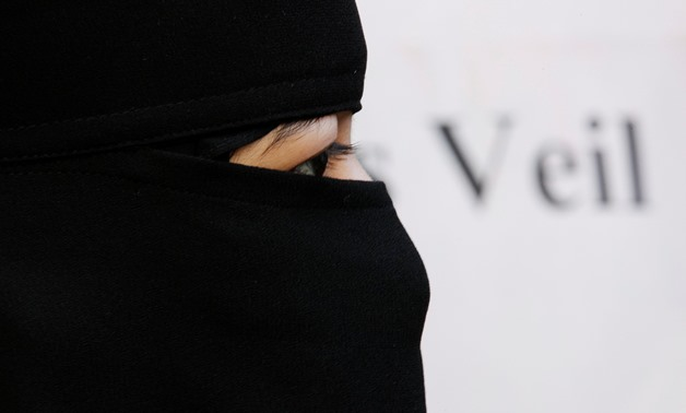 FILE PHOTO: A Muslim woman takes part in a demonstration outside the French Embassy in London September 25, 2010. REUTERS/Luke MacGregor