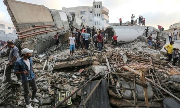 People inspect the rubble of a building after an Israeli air strike on Gaza City, which Palestinians say housed a cultural centre while the Israeli army says it was used by the Islamist Hamas group