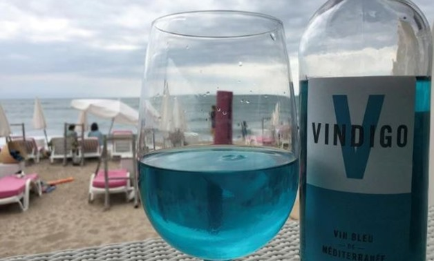 A glass of Vindigo, Mediterranean chardonnay wine, is seen at a beachfront restaurant in Sete, France, August 9, 2018. The wine is filtered through a pulp of red grape skins which contain a natural pigment, anthocyanin, and gives the wine its blue colour.