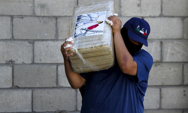 "FILE PHOTO: An agent of the office of the Attorney General of Mexico carries a package of seized marijuana at the site of a passageway Mexican authorities on Thursday attributed to the cartel of fugitive kingpin Joaquin ""El Chapo"" Guzman in Tijuana, Octob"