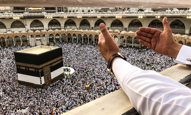 A muslim pilgrim prays while others circle the Kaaba and pray at the Grand mosque ahead of annual Haj pilgrimage in the holy city of Mecca, Saudi Arabia August 16, 2018.REUTERS/Zohra Bensemra
