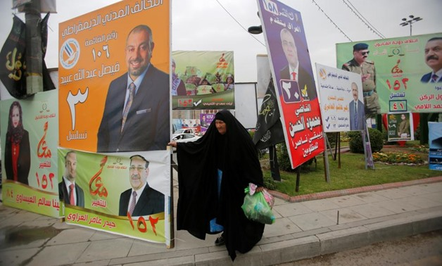 A woman walks past campaign posters of candidates ahead of parliamentary election, in Baghdad, Iraq April 22, 2018. REUTERS/Khalid al Mousily