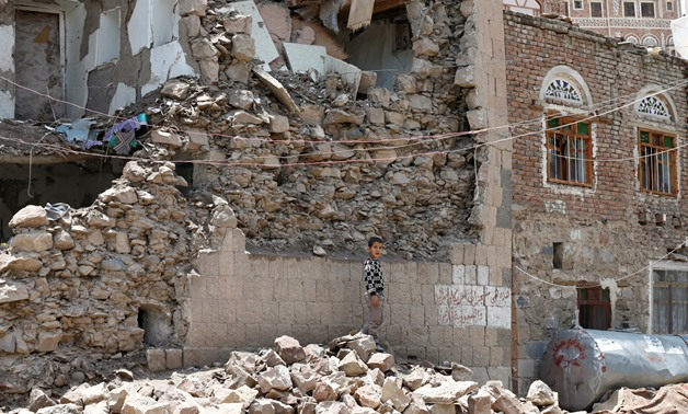A boy stands next to a house destroyed by an air strike in the old quarter of Sanaa, Yemen August 8, 2018. Picture taken August 8, 2018. REUTERS/Khaled Abdullah