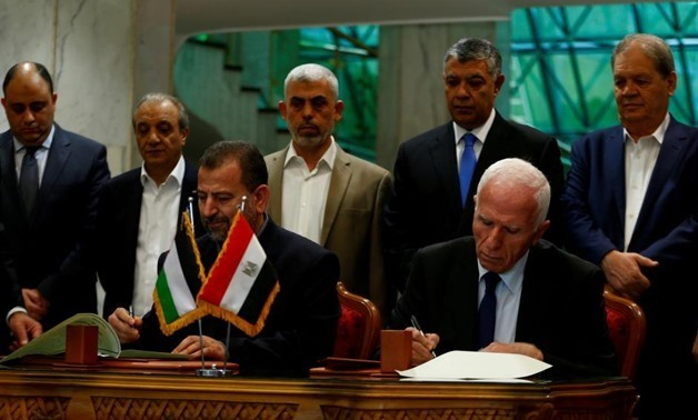 FILE - Head of Hamas delegation Saleh Arouri and Fatah leader Azzam Ahmad sign a reconciliation deal in Cairo, Egypt, October 12, 2017.