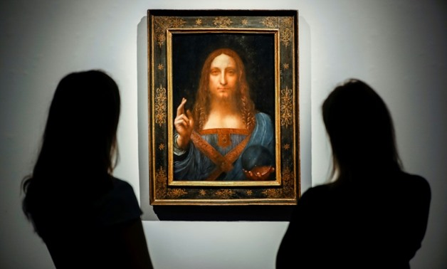 Christie's employees pose in front of a painting entitled Salvator Mundi and attributed to Leonardo da Vinci at a photocall at the auction house in central London on October 22, 2017 a month ahead of its sale.