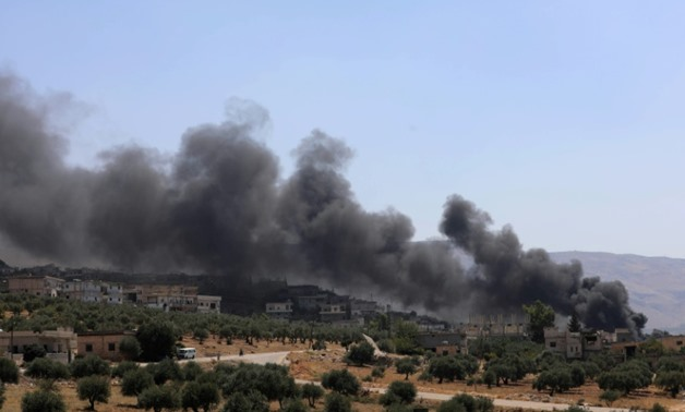 Smoke blows from buildings reportedly hit by Russian air strikes in the rebel-held town of Muhambal, Idlib province, on September 4, 2018