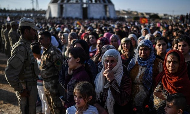 A picture taken on October 14, 2017 in the Kurdish town of Kobane in northern Syria shows people gathering for the funeral of a Kurdish fighter, who was killed in clashes against Islamic State (IS) group fighters in the city of Deir Ezzor. (AFP Photo)