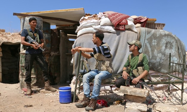 "Syrian rebel fighters from the recently-formed ""National Liberation Front"" rest in the northern countryside of Idlib province on September 5, 2018"