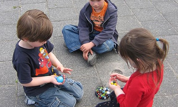 Kids playing with marbles- CC via Wikimedia