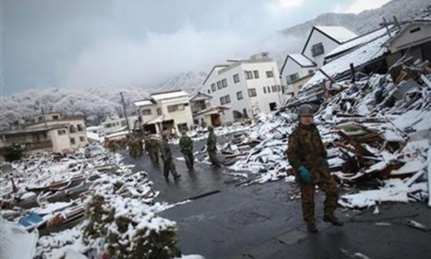 Members of the Japan Self Defence force walk through the snow-covered ruins of Kamaishi, Iwate Prefecture, days after the area was devastated by a magnitude 9.0 earthquake and tsunami March 16, 2011. REUTERS/Damir Sagolj