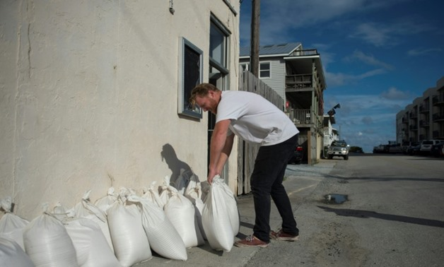 A man prepares sandbags outside a shop in Wrightsville Beach, North Carolina, ahead of the arrival of Hurricane Florence