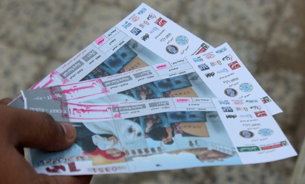 """A Yemeni man shows tickets for the movie """"10 Days Before the Wedding"""" in front of a makeshift cinema in the southern city of Aden on September 13, 2018."""