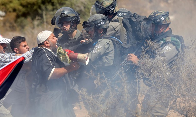 Palestinians scuffle with Israeli troops during a protest against Israeli land seizures for Jewish settlements, in the village of Ras Karkar, near Ramallah in the occupied West Bank September 14, 2018. REUTERS/Mohamad Torokman
