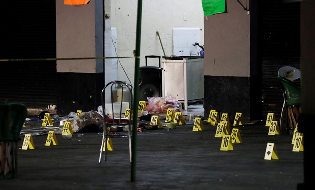 Evidence markers are seen at a crime scene where three men were gunned down by unknown assailants at an intersection on the edge of tourist Plaza Garibaldi in Mexico City, Mexico September 14, 2018. REUTERS/Henry Romero