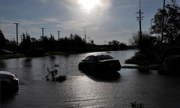 The sun reflects on flood water and stranded vehicles as it emerges after days of storm clouds and rain, in the aftermath of Hurricane Florence in Wilmington, North Calorina, U.S., September 17, 2018. REUTERS/Jonathan Drake