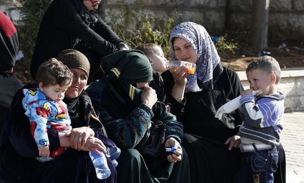 Syria women and children wait to get a visa stamp to enter Lebanon. Credit: Jamal Saidi/ Reuters
