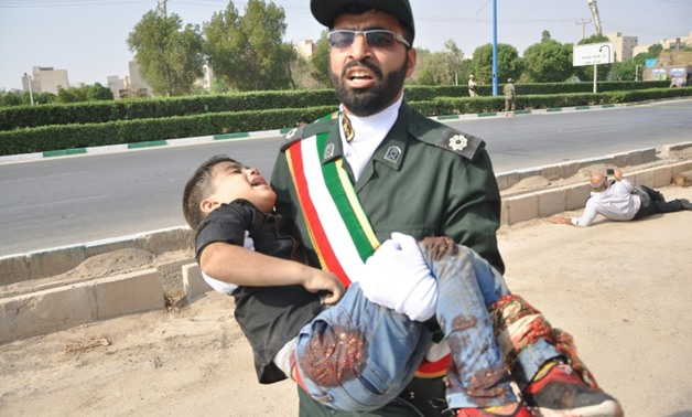 A member of Iran's elite Revolutionary Guards carries away a child wounded in a shooting rampage at a military parade in the southwestern city of Ahvaz that Foreign Minister Mohammed Javad Zarif blamed on a US ally in the region