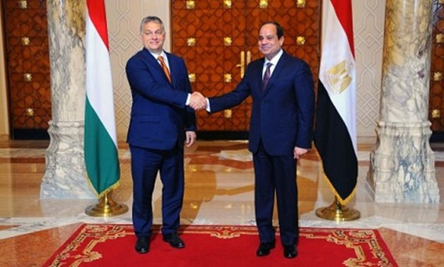A handout picture released by the Egyptian Presidency shows Egyptian President Abdel Fattah El-Sisi (R) shaking hands with Hungarian Prime Minister Viktor Orban at the Presidential Palace in Cairo on June 1, 2016.
