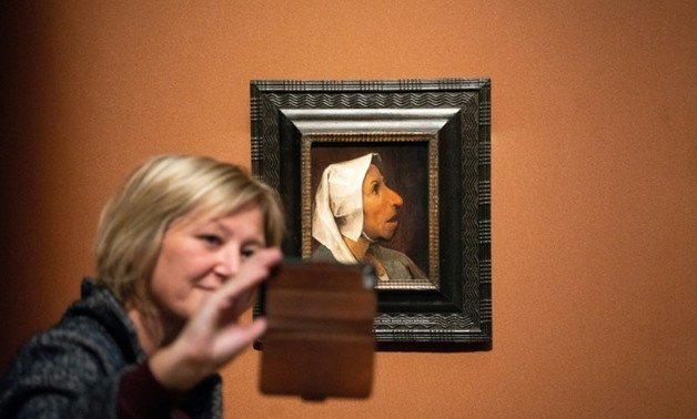 A visitor takes a selfie with the painting 'Head of a Peasant Woman' at the world's first monograph exhibition dedicated to Flemish master Pieter Bruegel the Elder in Vienna.