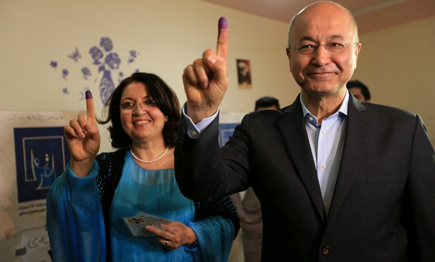 FILE PHOTO: Barham Salih, Former Prime Minister of Iraq's Kurdistan Regional Government and Head of the Coalition for Democracy and Justice with his wife show their ink-stained fingers after casting their votes at a polling station during the parliamentar
