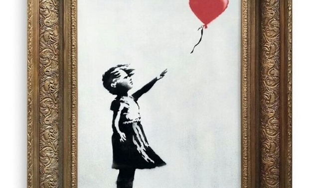 "A pre-sale photo supplied by Sotheby's in London on October 6, 2018 shows ""Girl with Balloon"" by the British artist Banksy, which sold on October 5 for £1,042,000 and then unexpectedly passed through a shredder hidden in the frame."