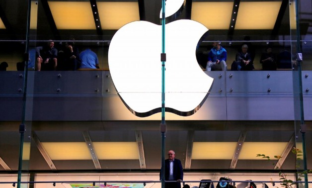 A customer stands underneath an illuminated Apple logo as he looks out the window of the Apple store located in central Sydney, Australia, May 28, 2018. REUTERS/David Gray