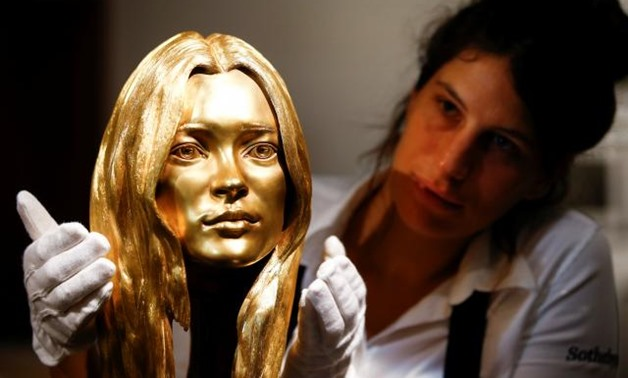 A Sotheby's employee poses with a bust of Kate Moss in solid 18-carat gold during a photocall for 'The Midas Touch' collection at Sotheby's in London, Britain, October 12, 2018. REUTERS/Henry Nicholls.