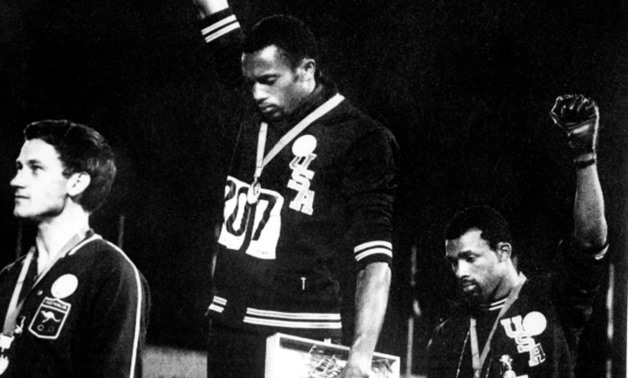 US athletes Tommie Smith (C) and John Carlos (R) raise their gloved fists in the Black Power salute against racism during their national anthem, after receiving their first and third place medals in the men's 200m event at the 1968 Mexico Olympics EPU/AF