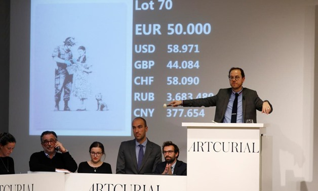 """Auctioneer Arnaud Oliveux reacts at the final price in the bidding of the offset lithograph entitled """"Stop and Search"""" (2007) by British street artist Banksy at the urban art auction organized by Artcurial in Paris, France, October 24, 2018. REUTERS/Charl"""
